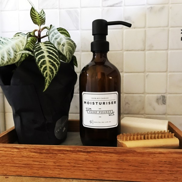 Matte black soap dispenser with amber glass bottle on tray